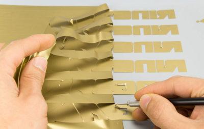 Adesivo prespaziato in materiale vinilivo dorato, sagomato con lettere del logo, prodotto da Serit Etichette